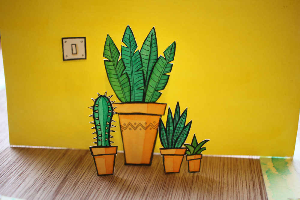 A Photo of papercut paintings of plants on a yellow background.