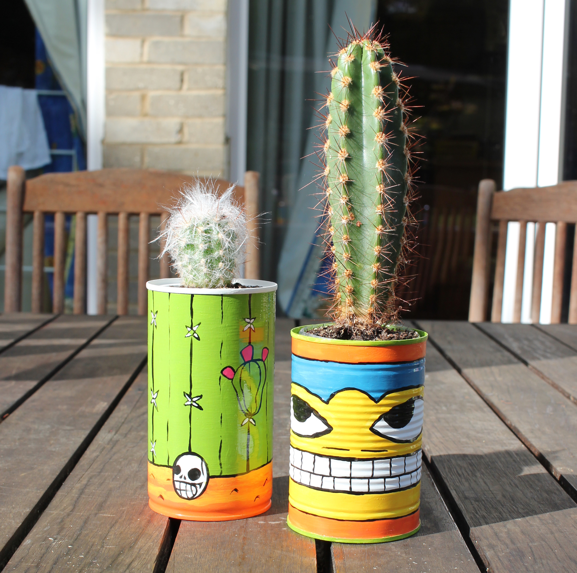 An image of two cactus pots with cacti. the pots are made from up-cycled tin cans. they are painted in a mexican art style in bright and vivid enamel paint.