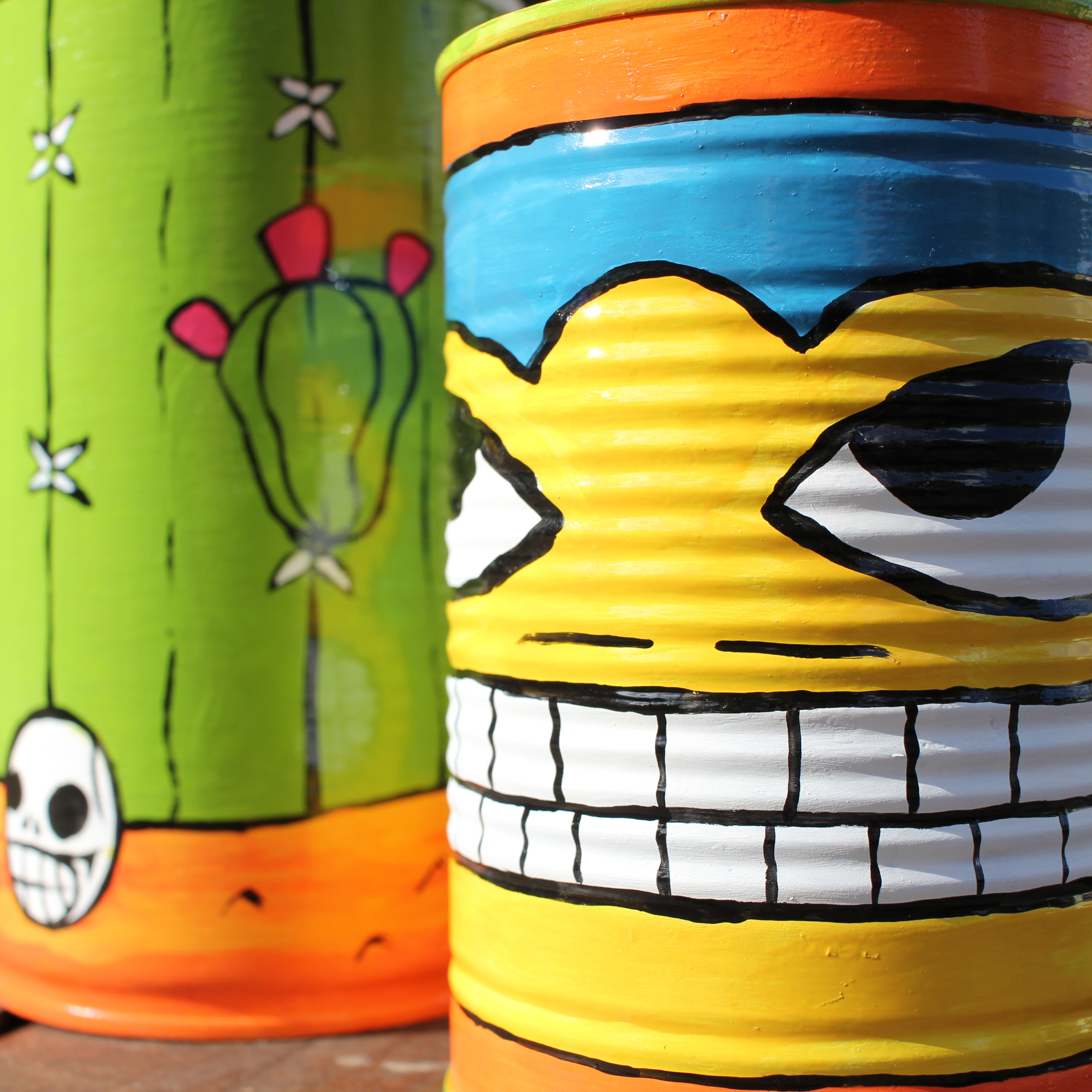 A phot of two tin cans painted in a mexican style using enamel paints. They are very bright. one resembles a mexican wrestler, the other resembles a cactus in the desert with a skull.